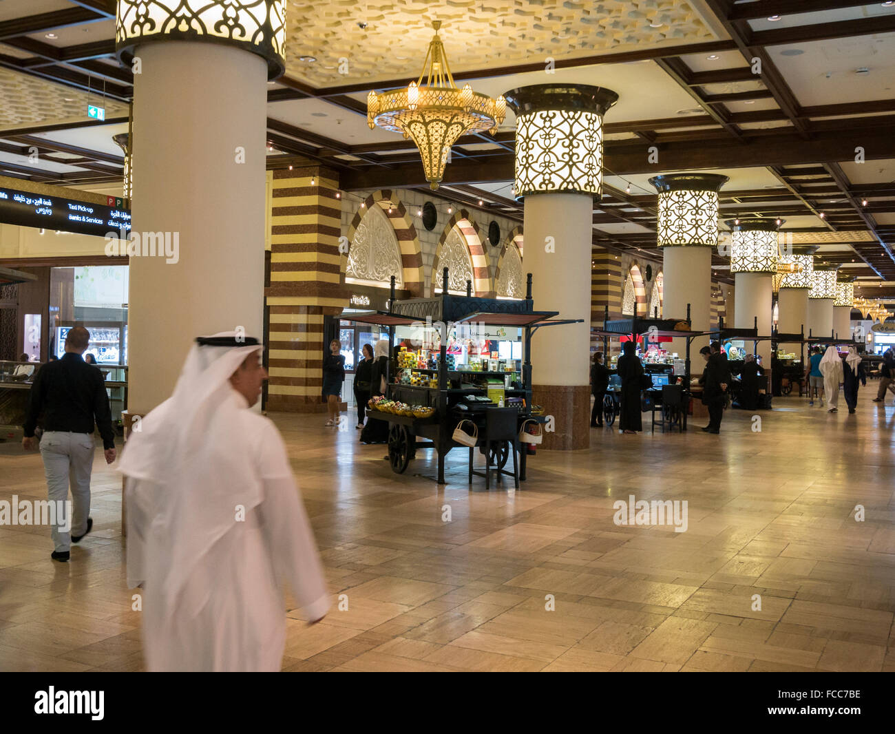 Tourists, immigrant families and local residents shopping in The Dubai Mall, the home of the Dubai shopping festival, - Stock Image