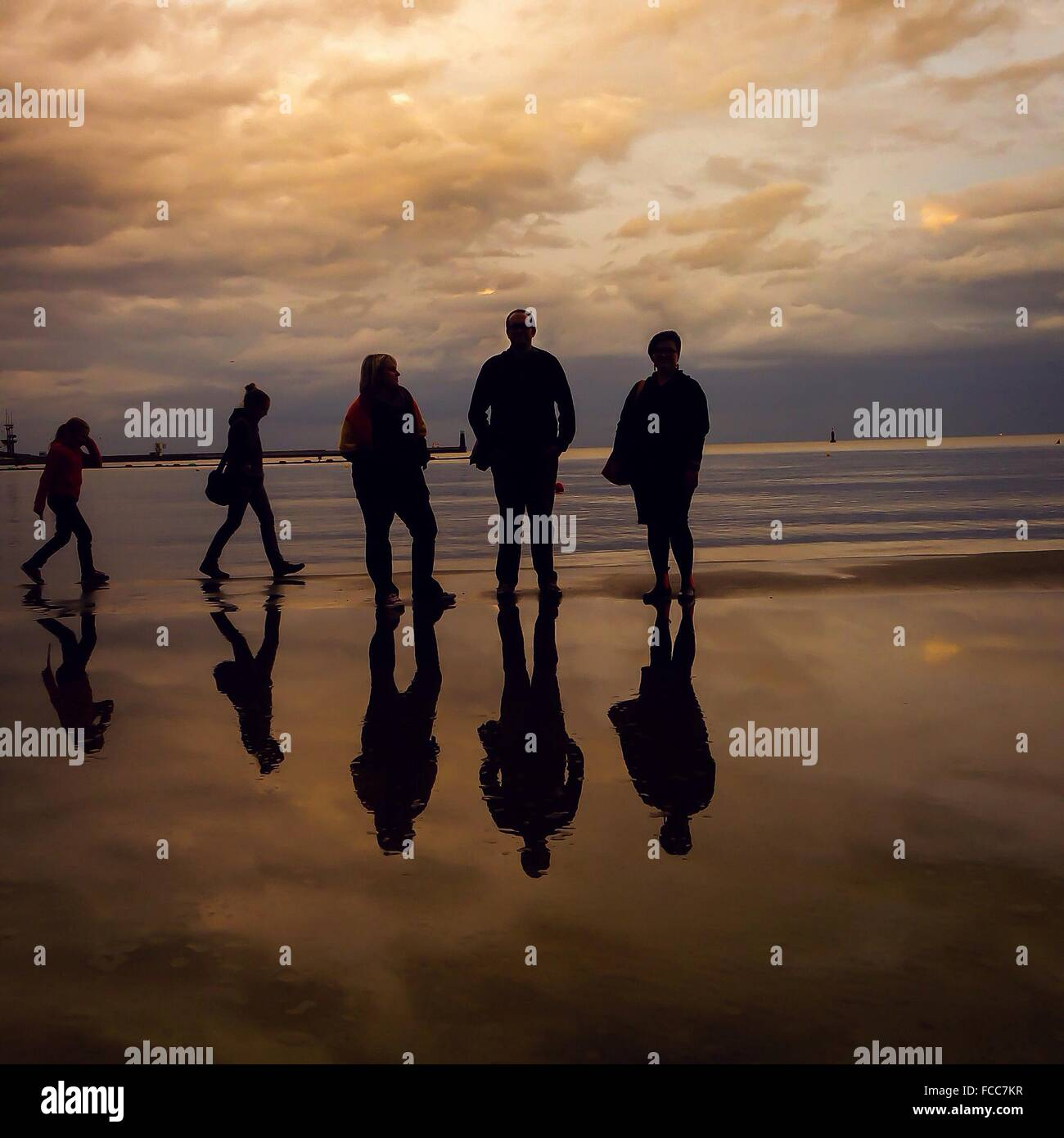 Silhouette People On Beach At Dusk - Stock Image