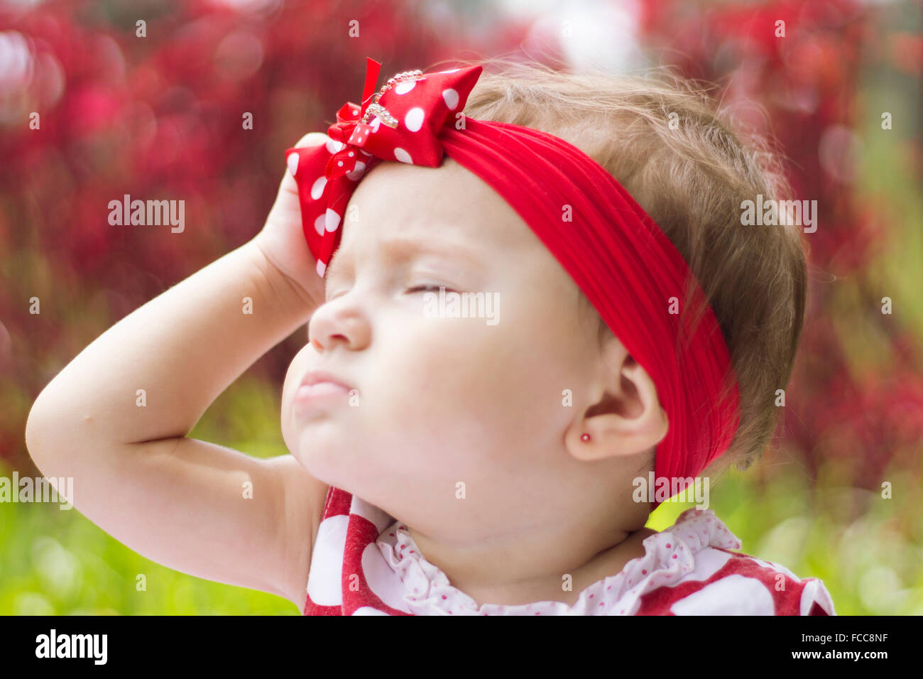 Close-Up Of A Pretty Baby Girl With Eyes Closed - Stock Image
