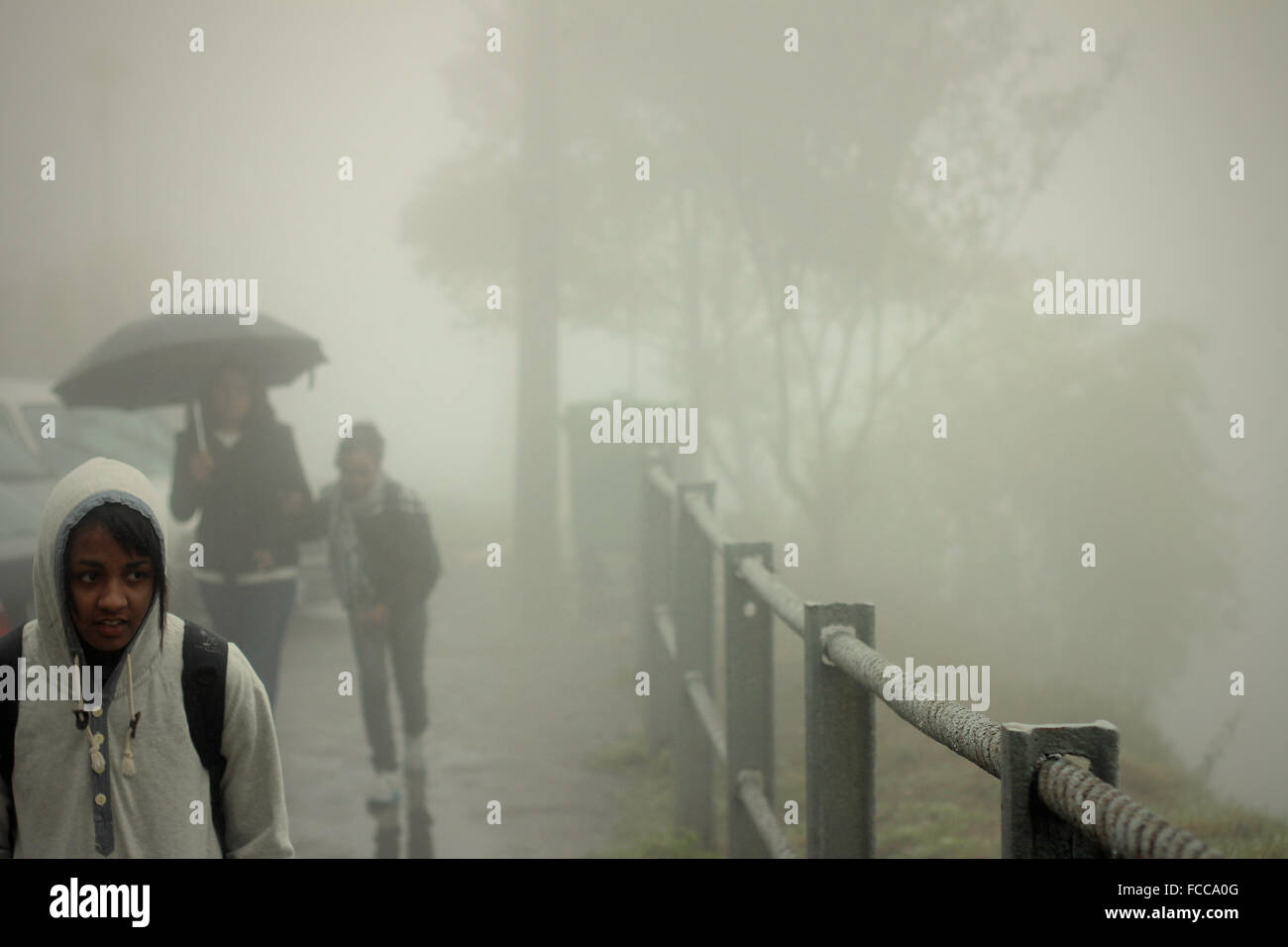 Girl Walking On Street During Foggy Weather Stock Photo