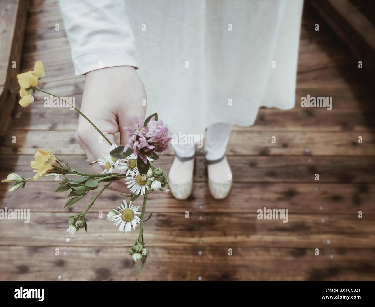 Woman Standing On Boardwalk Holding Flowers Stock Photo