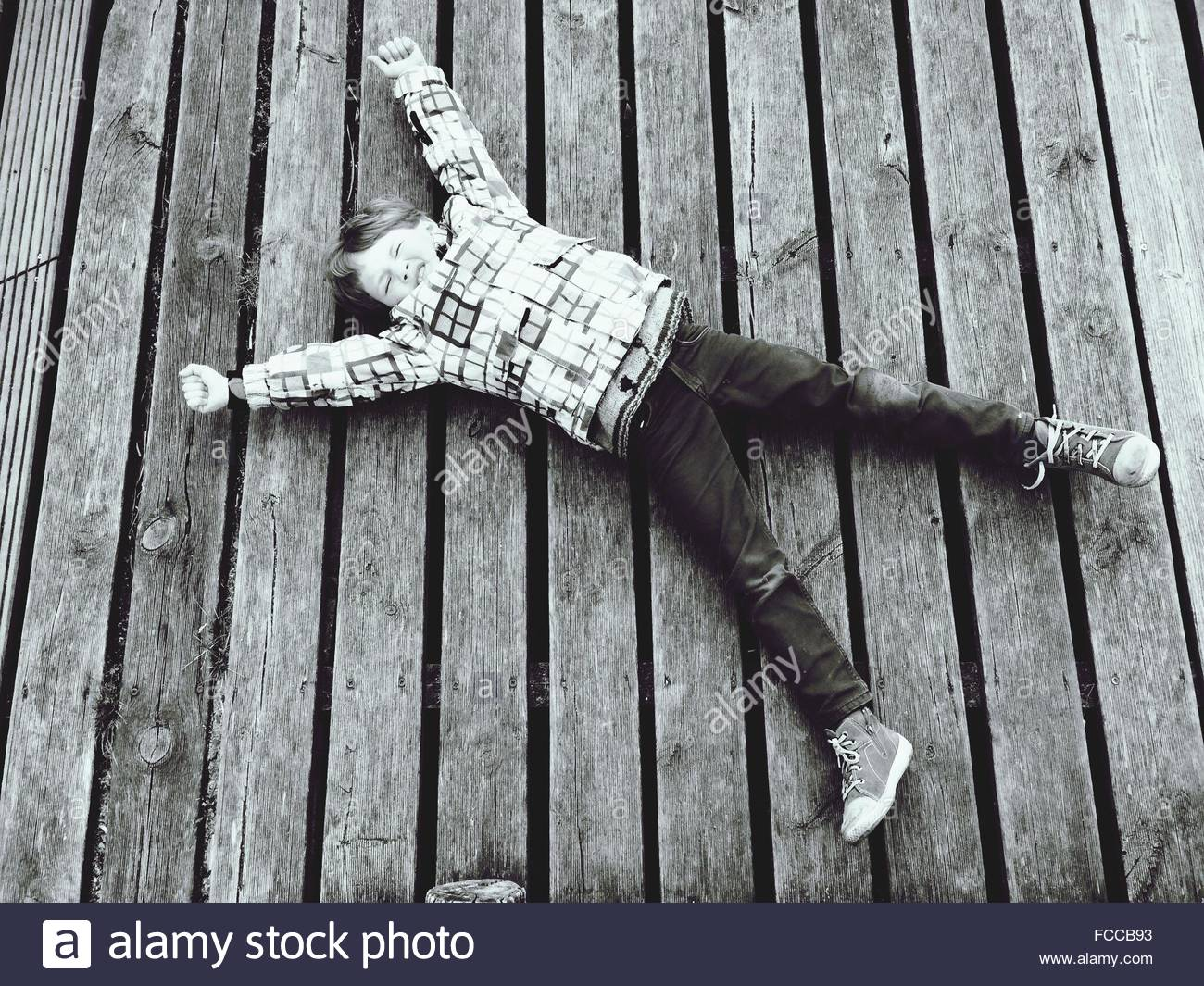 Full Length Of Boy Stretching While Lying On Boardwalk - Stock Image