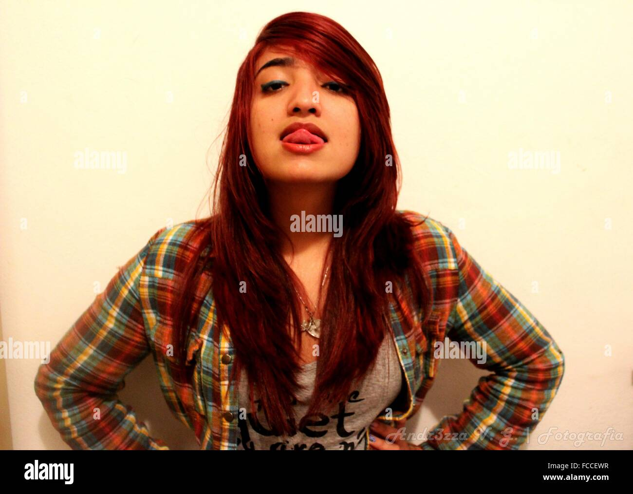 Portrait Of Young Woman Sticking Out Tongue Against White Background - Stock Image