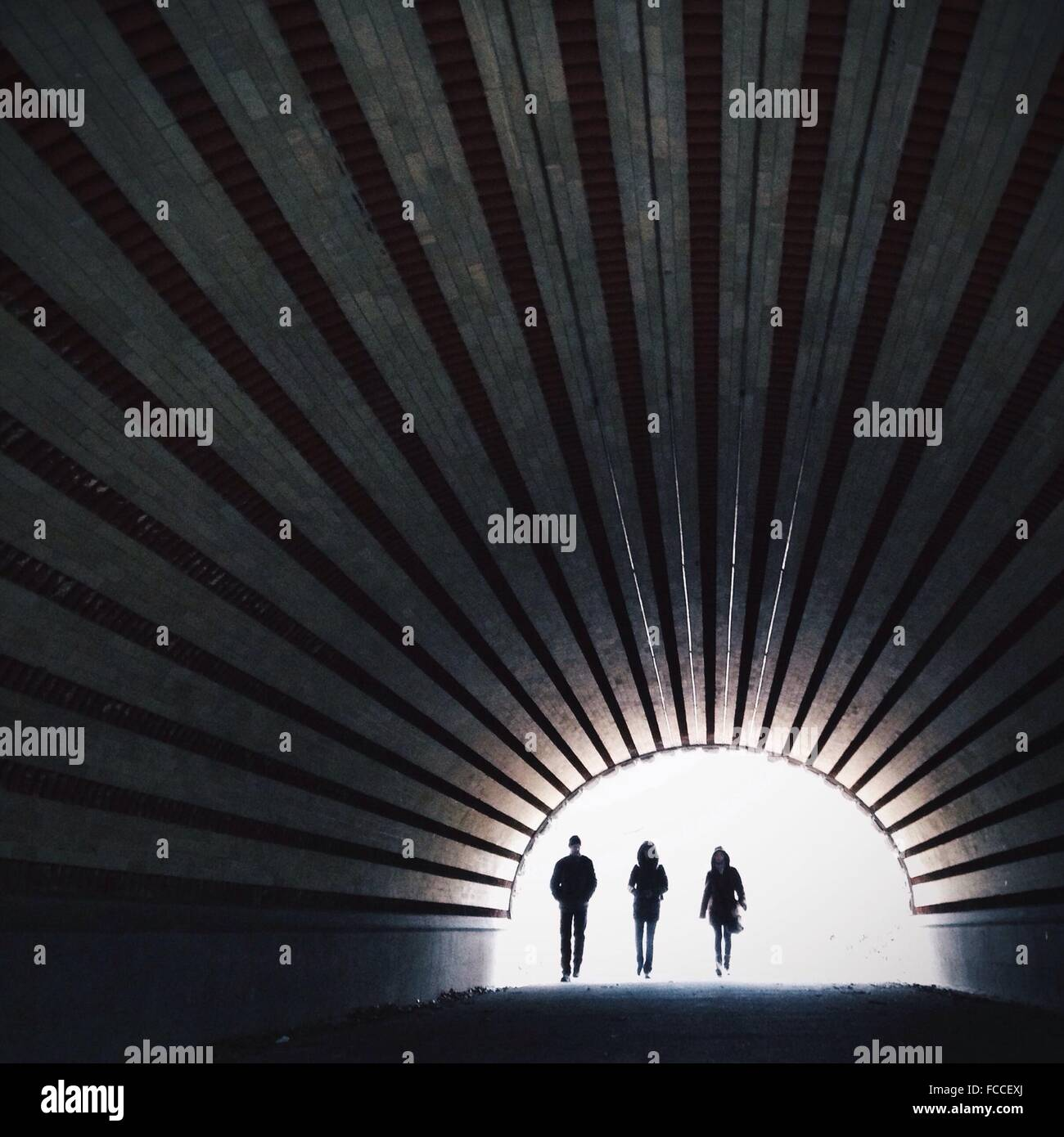 Full Length Of People Walking In Tunnel Stock Photo