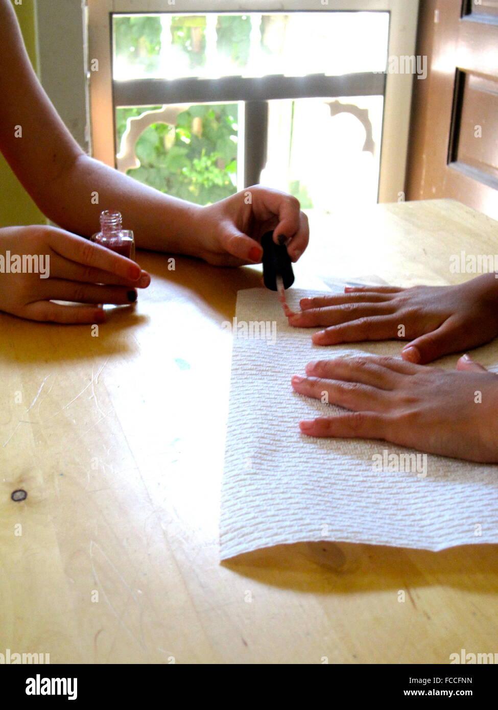 Close-Up Of Hands Applying Nail Varnish - Stock Image