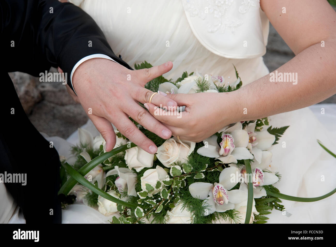 Woman Putting Wedding Ring On Man's Finger, Mid Section - Stock Image