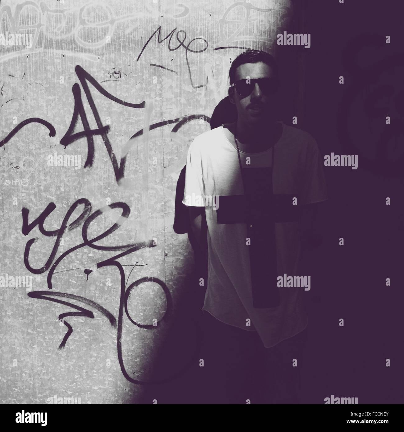 Man Standing By Graffiti - Stock Image