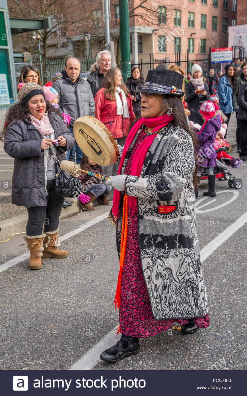 First Nations woman beating drum, Vancouver, British Columbia, Canada - Stock Image