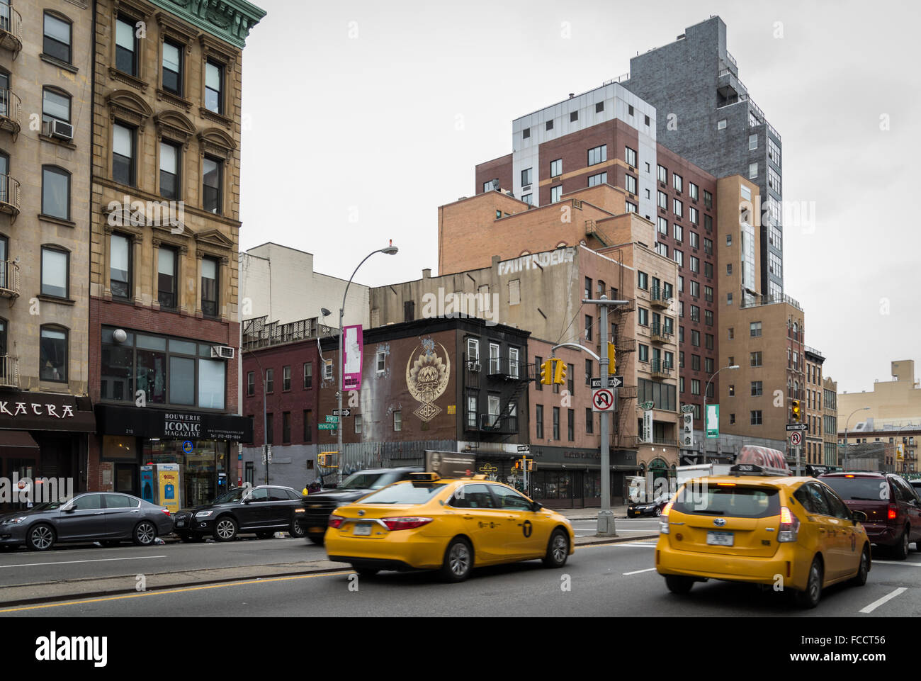Street view of the Bowery in Lower East Side, New York City. With yellow taxi cabs, architecture and graffiti. - Stock Image
