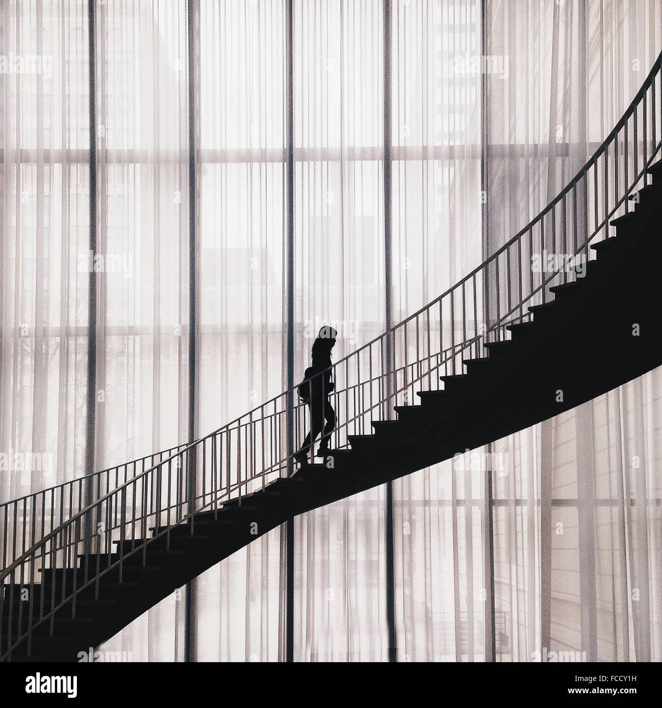 Silhouette Woman Walking On Staircase In Building - Stock Image