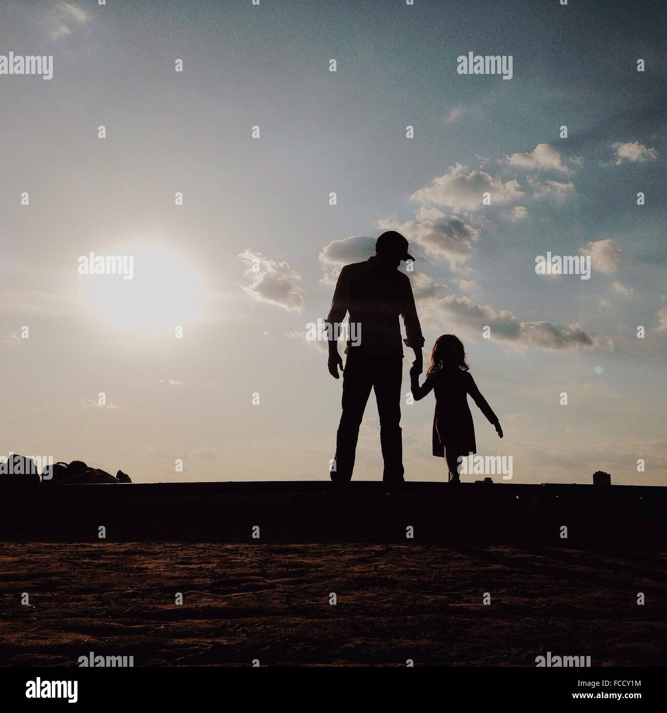 Silhouette Father With Daughter Standing On Field Against Sky - Stock Image