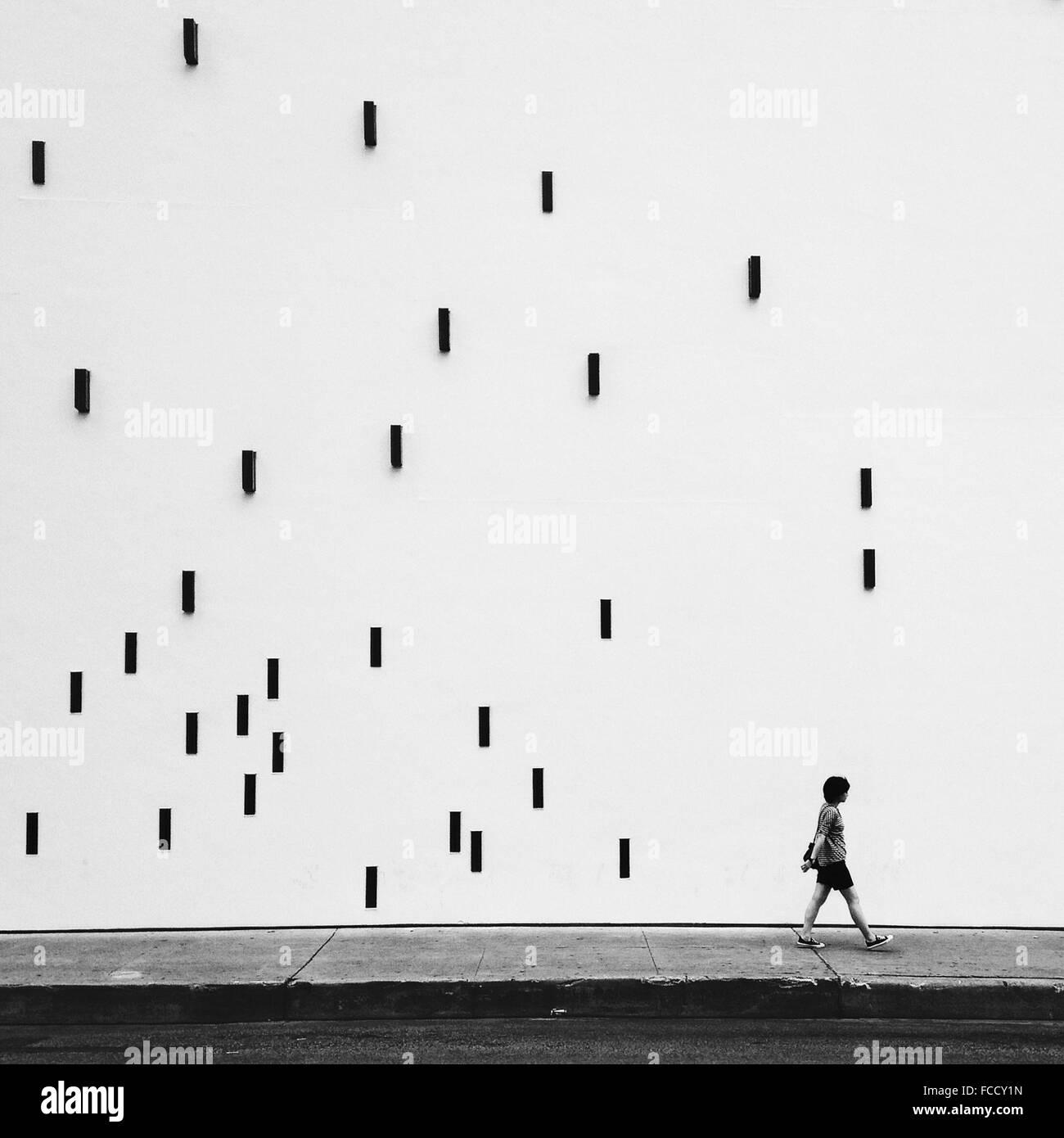 Man Walking On Sidewalk By Artistic Wall - Stock Image