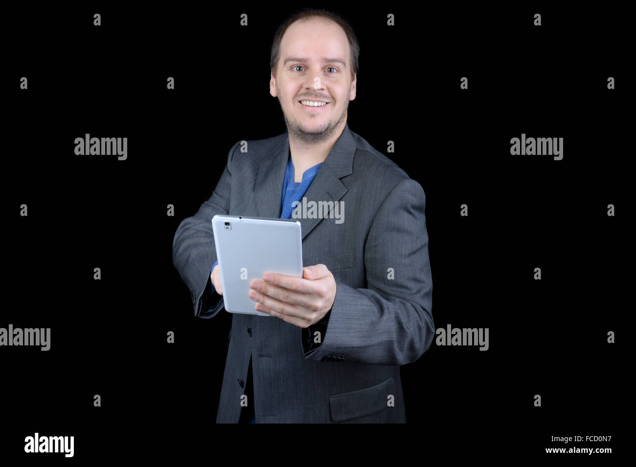 young man dark gray suit smiling pointing tablet - Stock Photo
