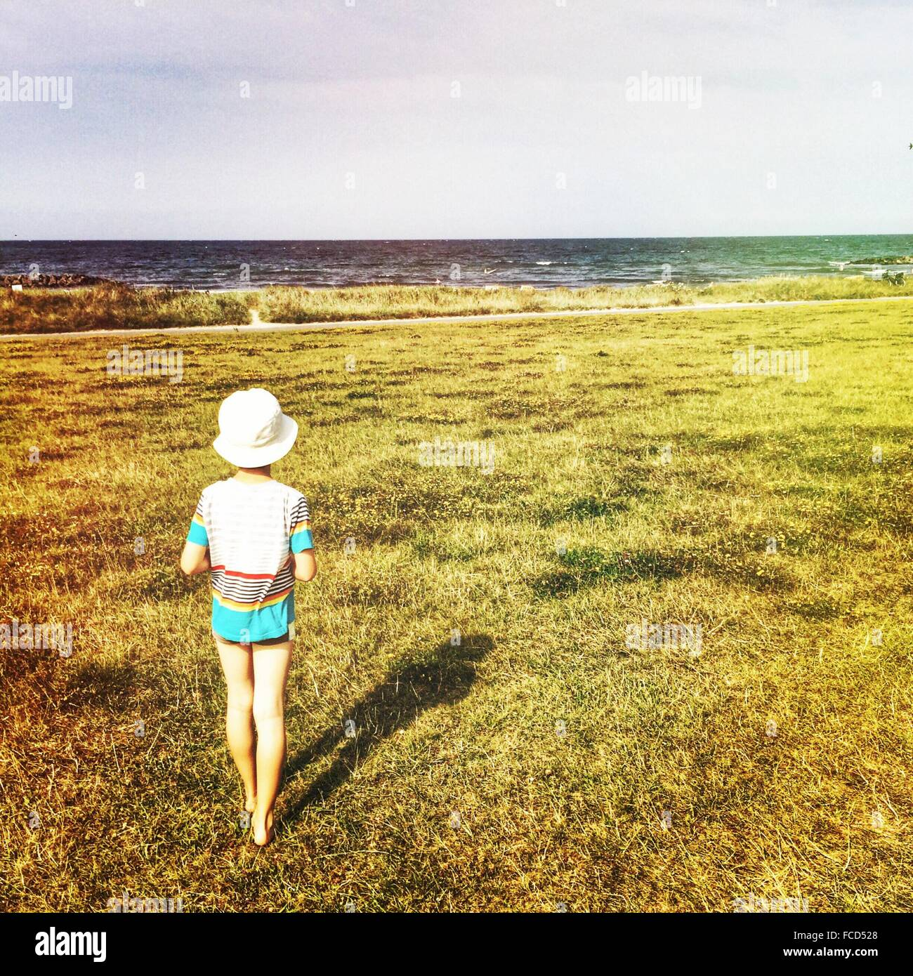 Rear View Of A Child Standing On Grass Looking At A View - Stock Image