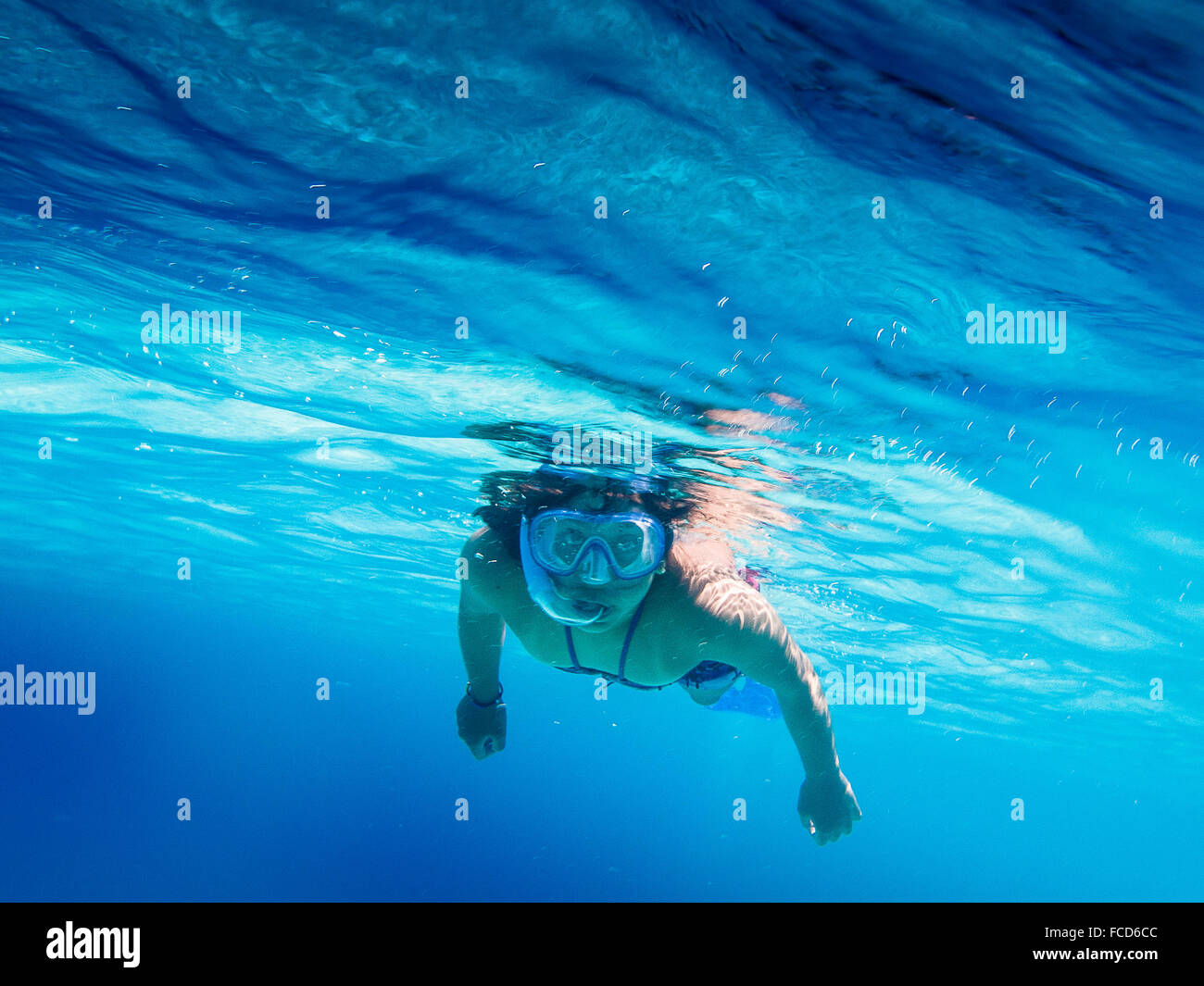 Portrait Of Woman Swimming In Blue Sea - Stock Image