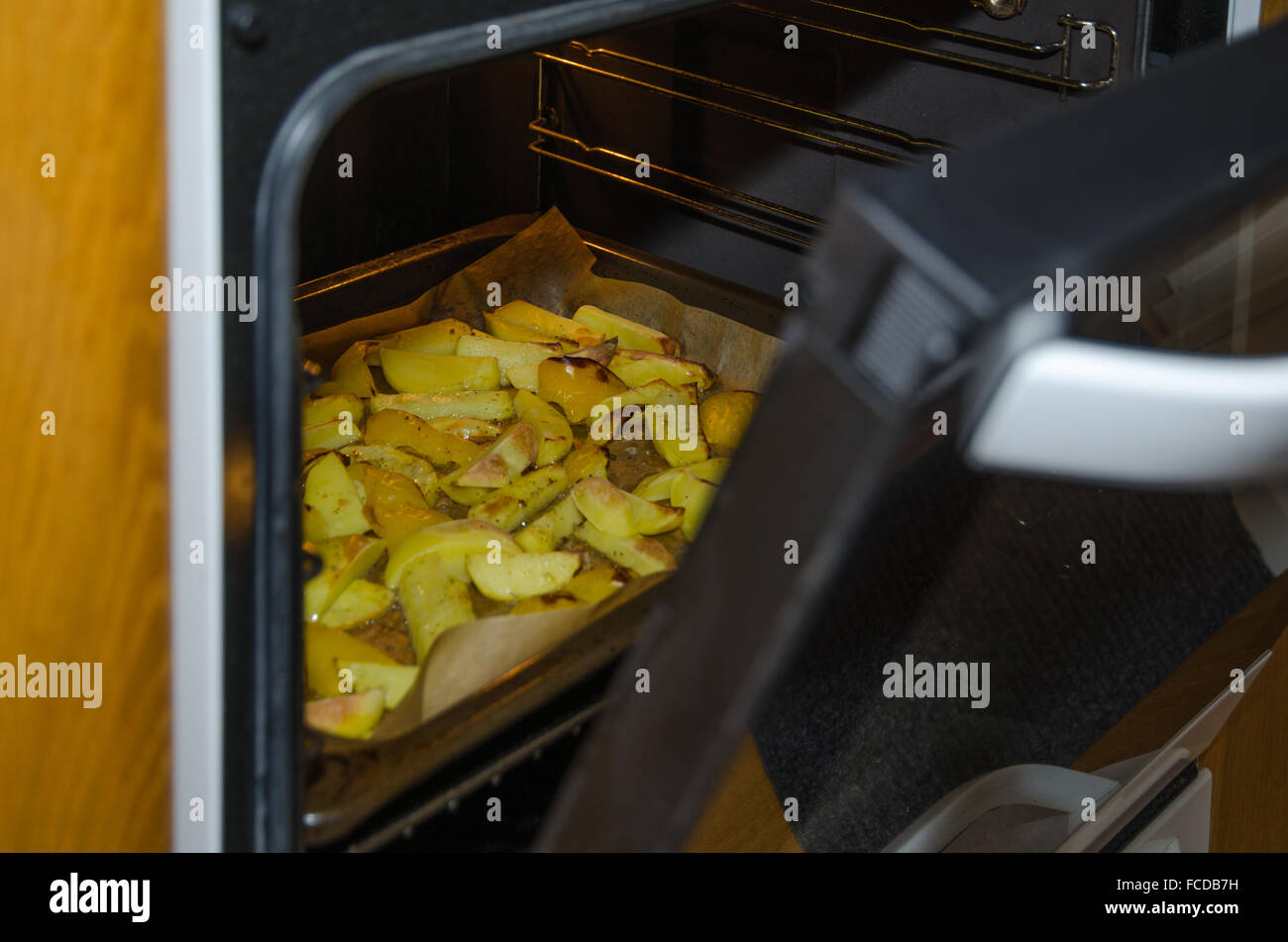 Glance into the oven with sliced roasted potatoes - Stock Image