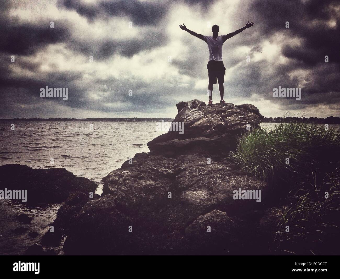 Man With Arms Outstretched Standing On Rocks Against Clouds Sky - Stock Image