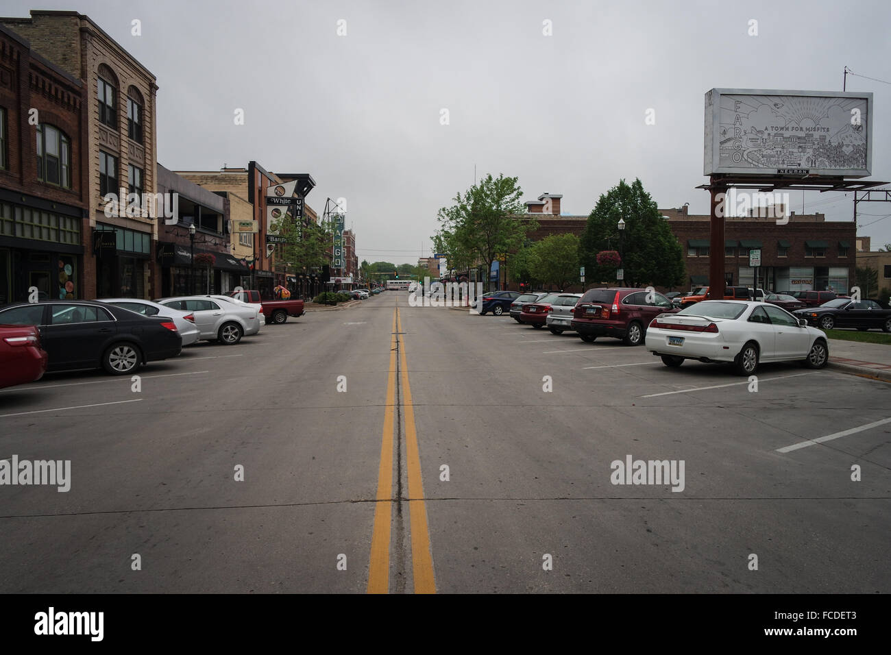 Double Yellow Line On Road In Diminishing Perspective, Cars Parked On Sides - Stock Image