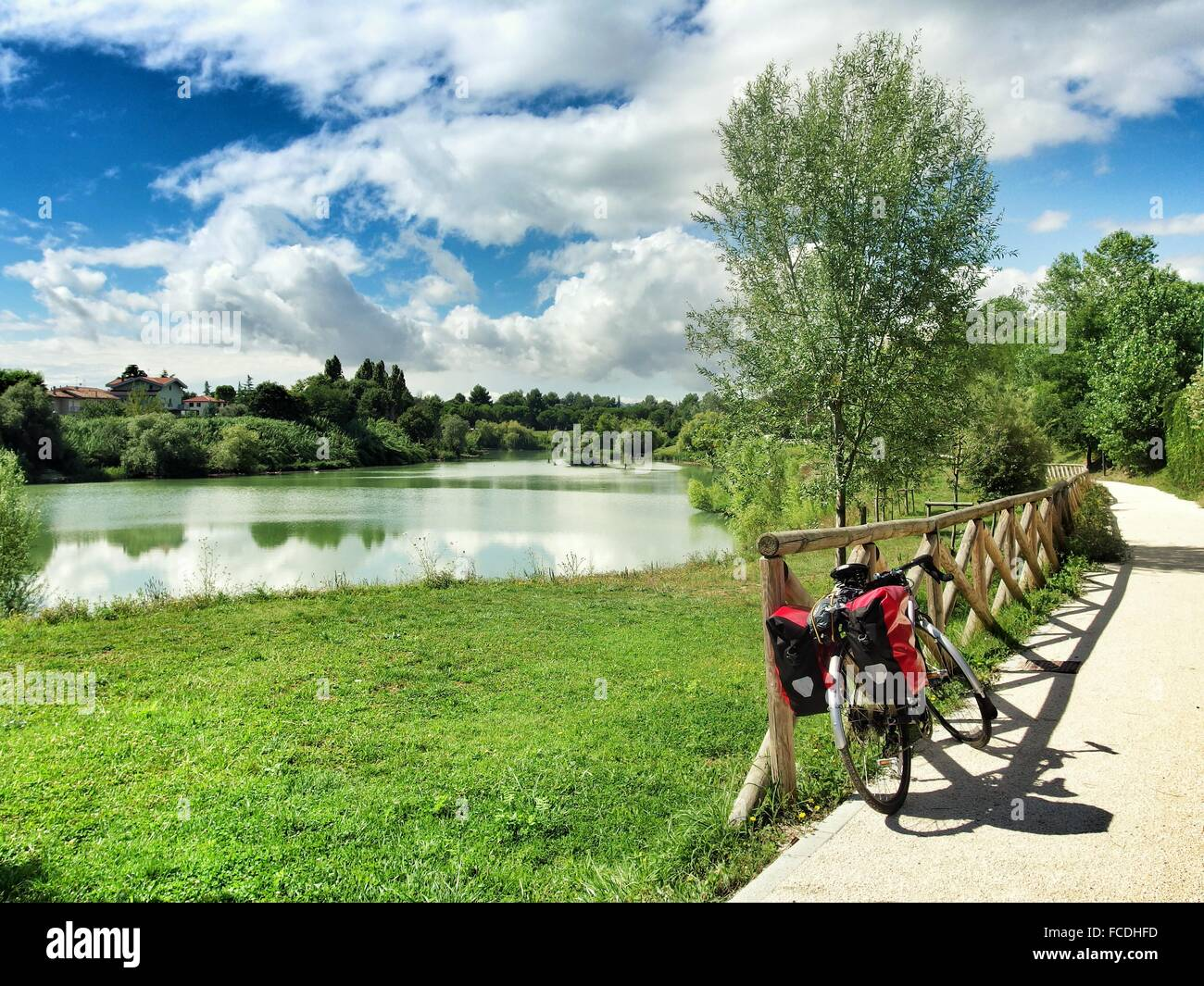 Bicycle Parked On Footpath By Lake Against Cloudy Sky Stock Photo
