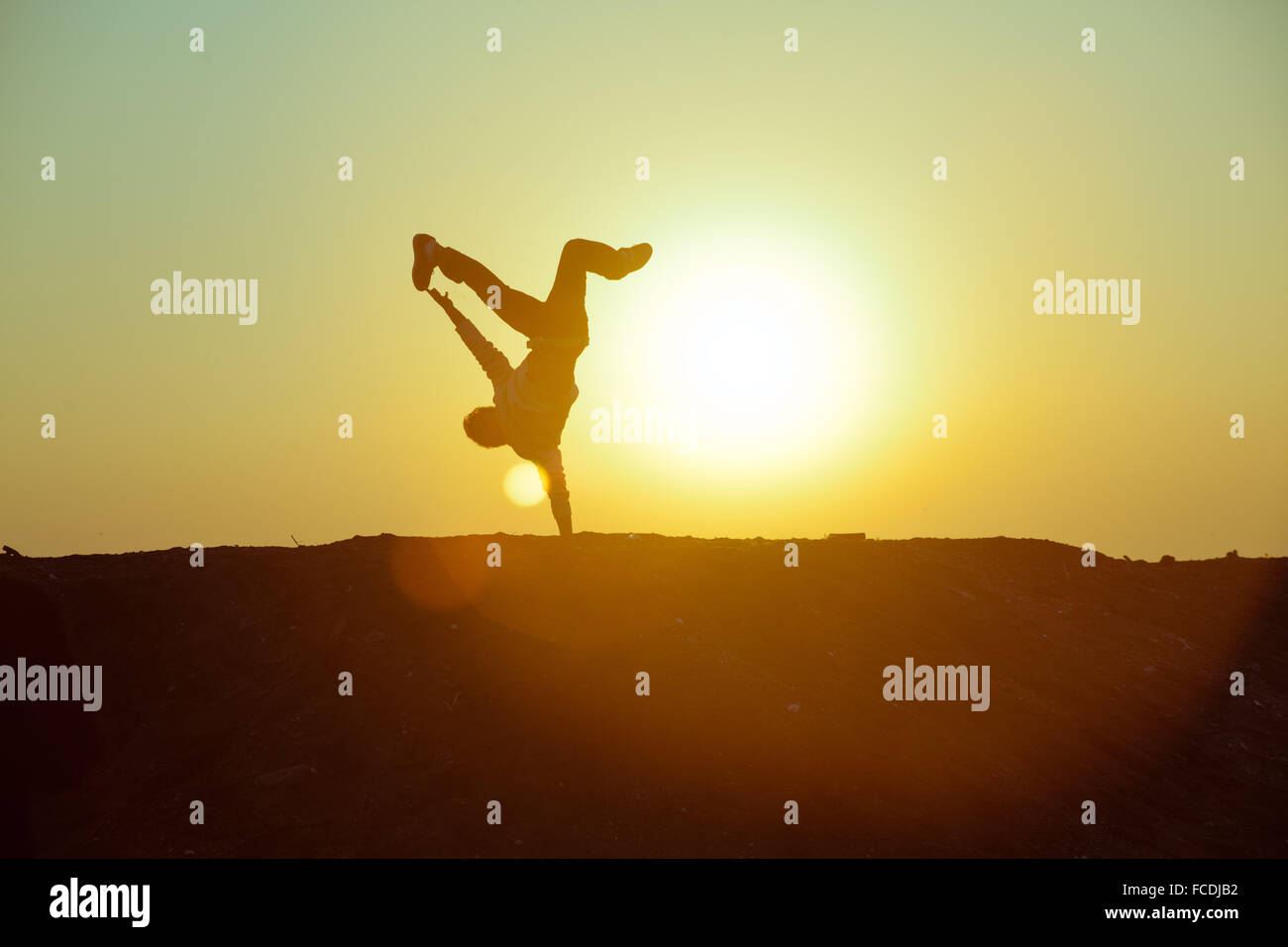 Silhouette Person Doing Handstand Against Sky During Sunset - Stock Photo