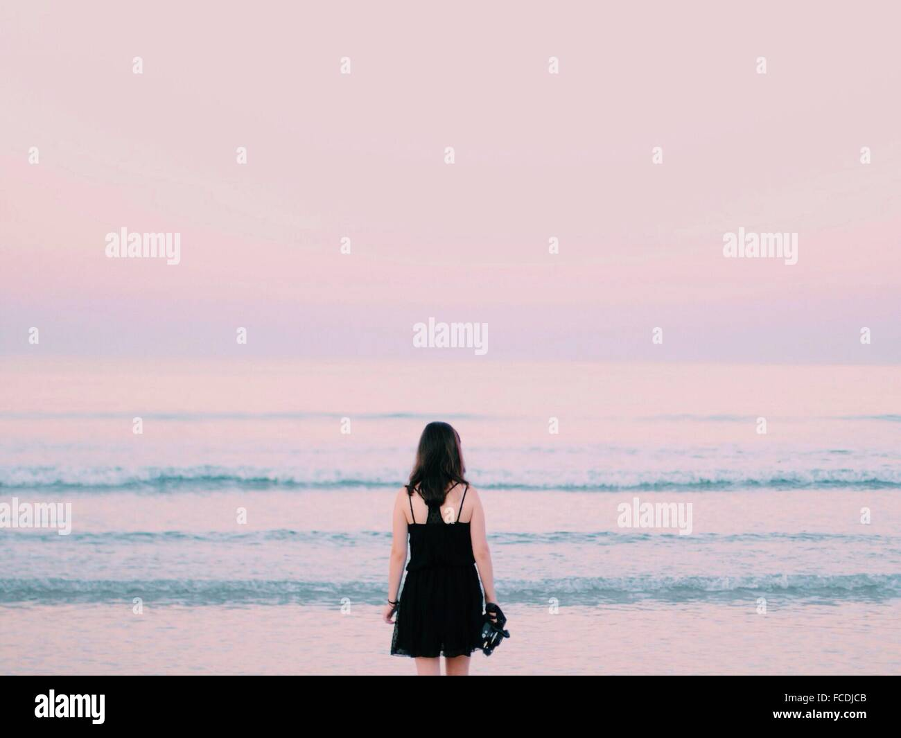 Rear View Of Woman Overlooking Calm Sea - Stock Image