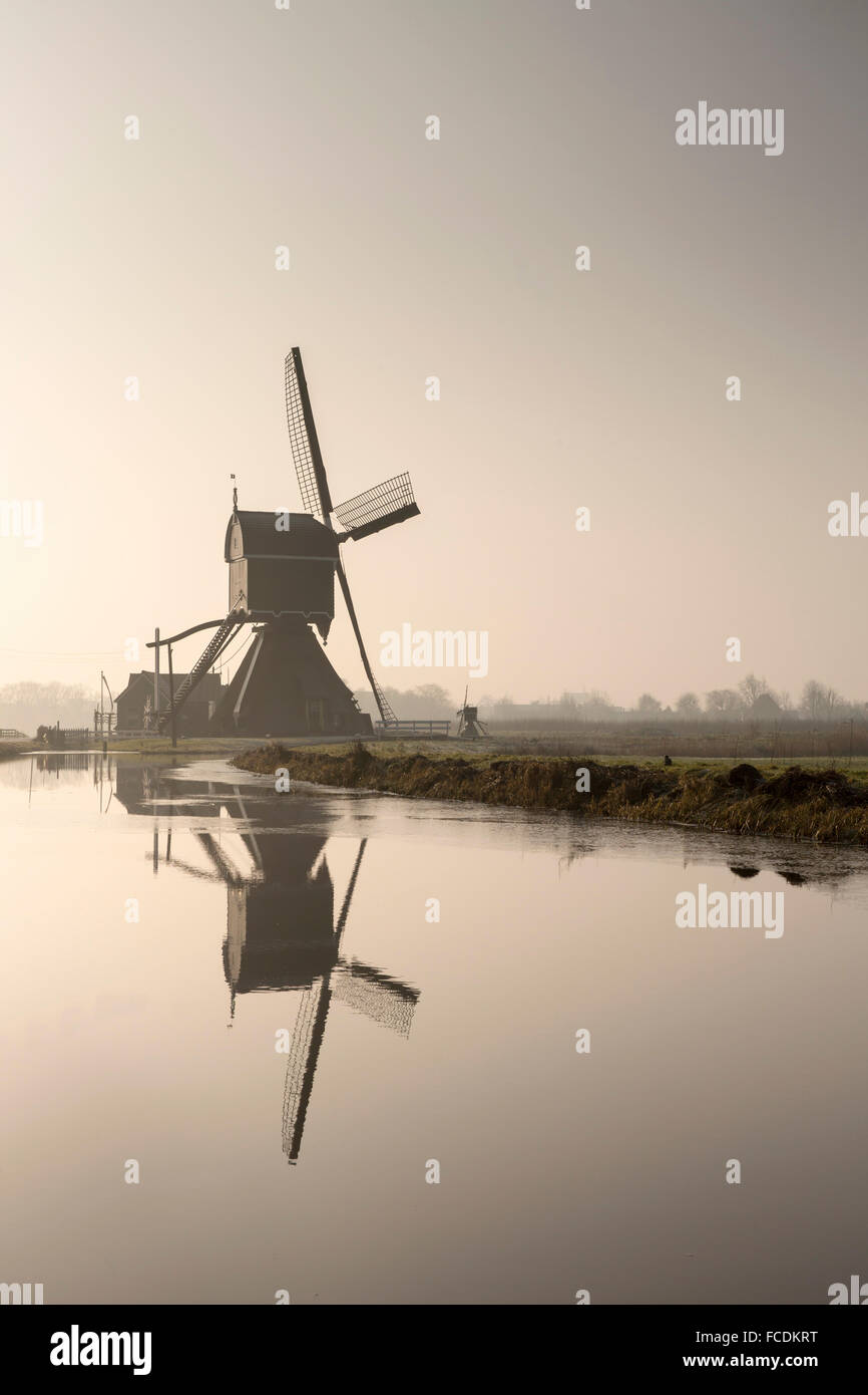 Netherlands, Vlist, Windmill pumping water from polder into belt canal. Winter - Stock Image