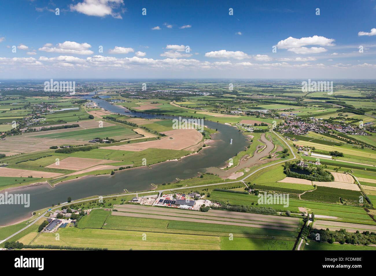 Netherlands, Lexmond, Cargo boat in river Lek. Farmland. Aerial - Stock Image