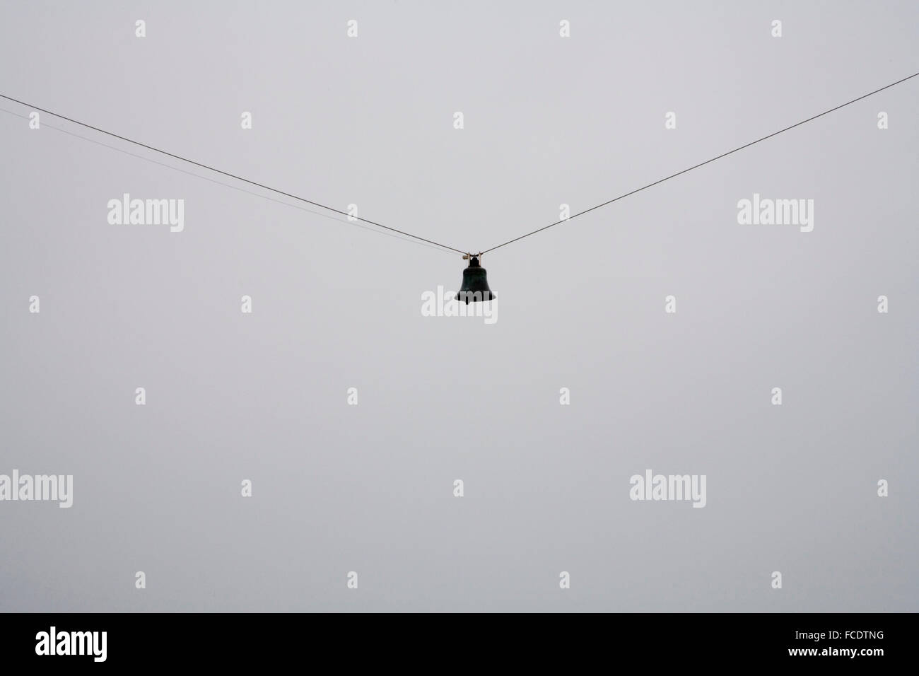Bell hanging on wire with grey sky - Stock Image