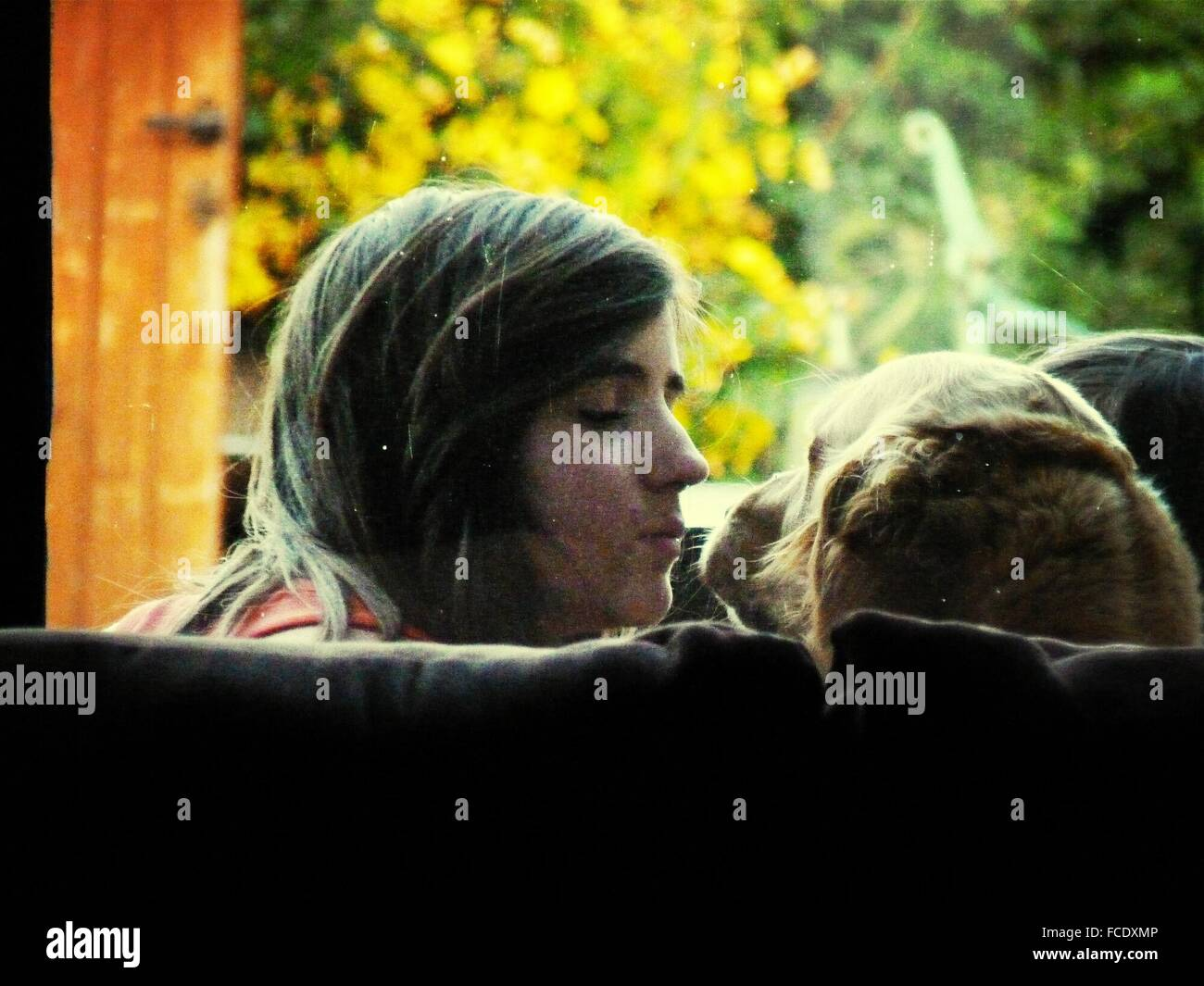 Woman Kissing Dog - Stock Image
