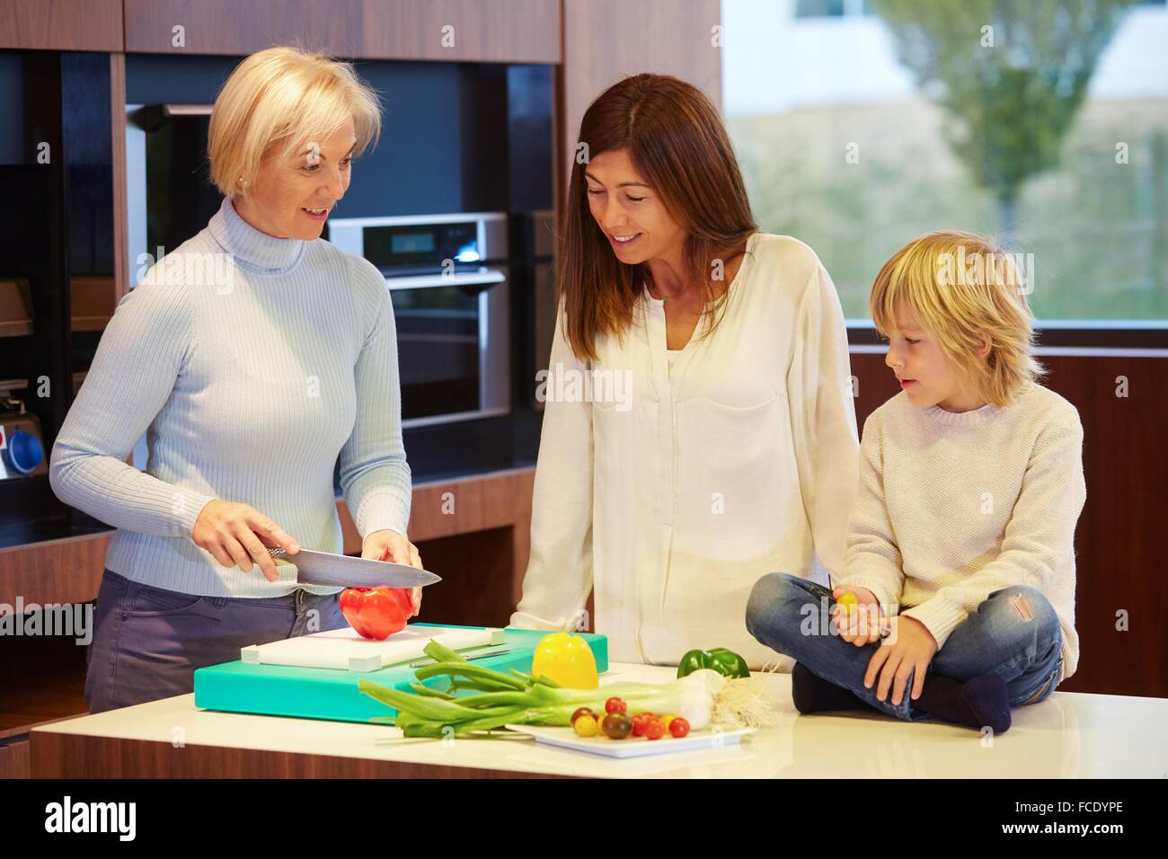 Family in the kitchen. Three generations. Healthy eating. Healthy growth. Vegetables. - Stock Image