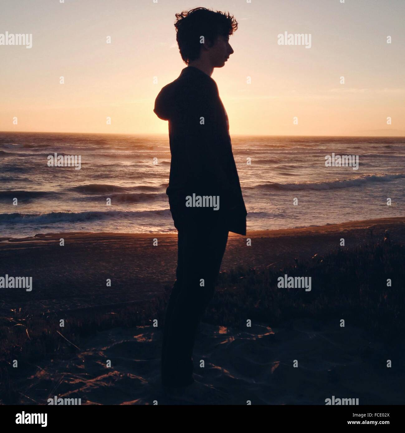 Side View Of Man Standing On Beach Against Sky - Stock Image