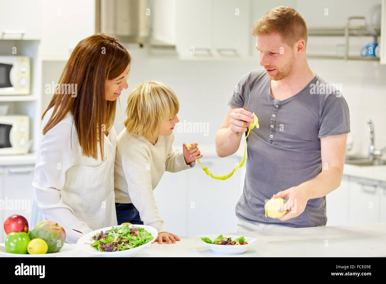 Family in the kitchen. Parents and son. Healthy eating. Healthy growth. Peeling an apple. - Stock Image