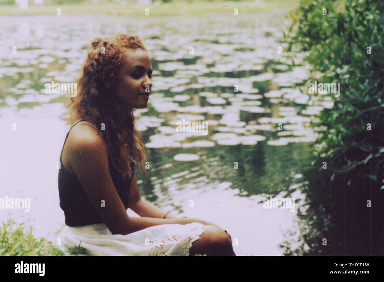Smiling Teenage Girl Looking Away By Lake - Stock Image