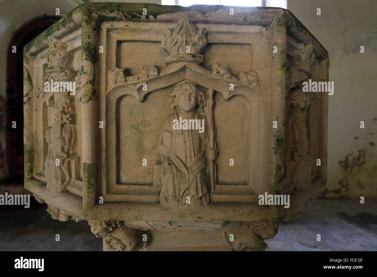 Detail from the 15th century stone font with carvings of the apostles, Possibly St Thomas holding a spear, St Nicholas - Stock Image