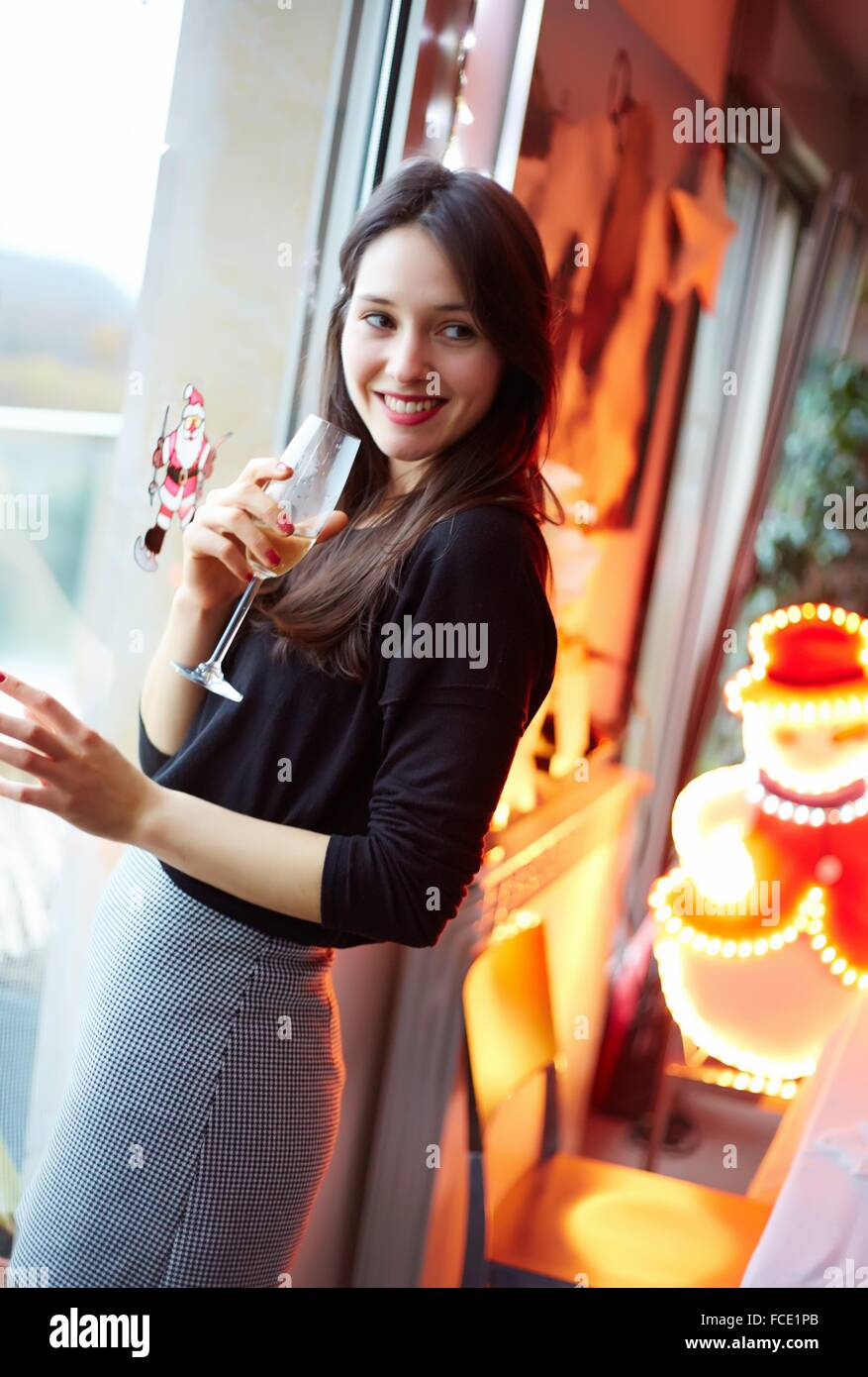 25 year old girl. Christmas. Glass of champagne. - Stock Image