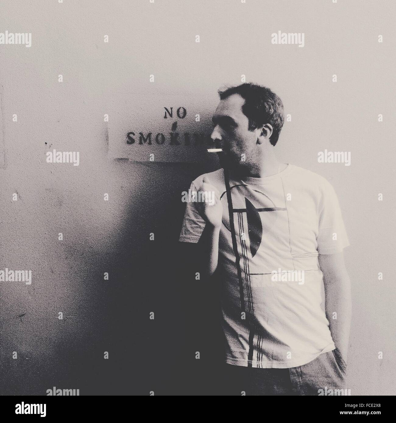 Man Smoking Against Warning Sign - Stock Image