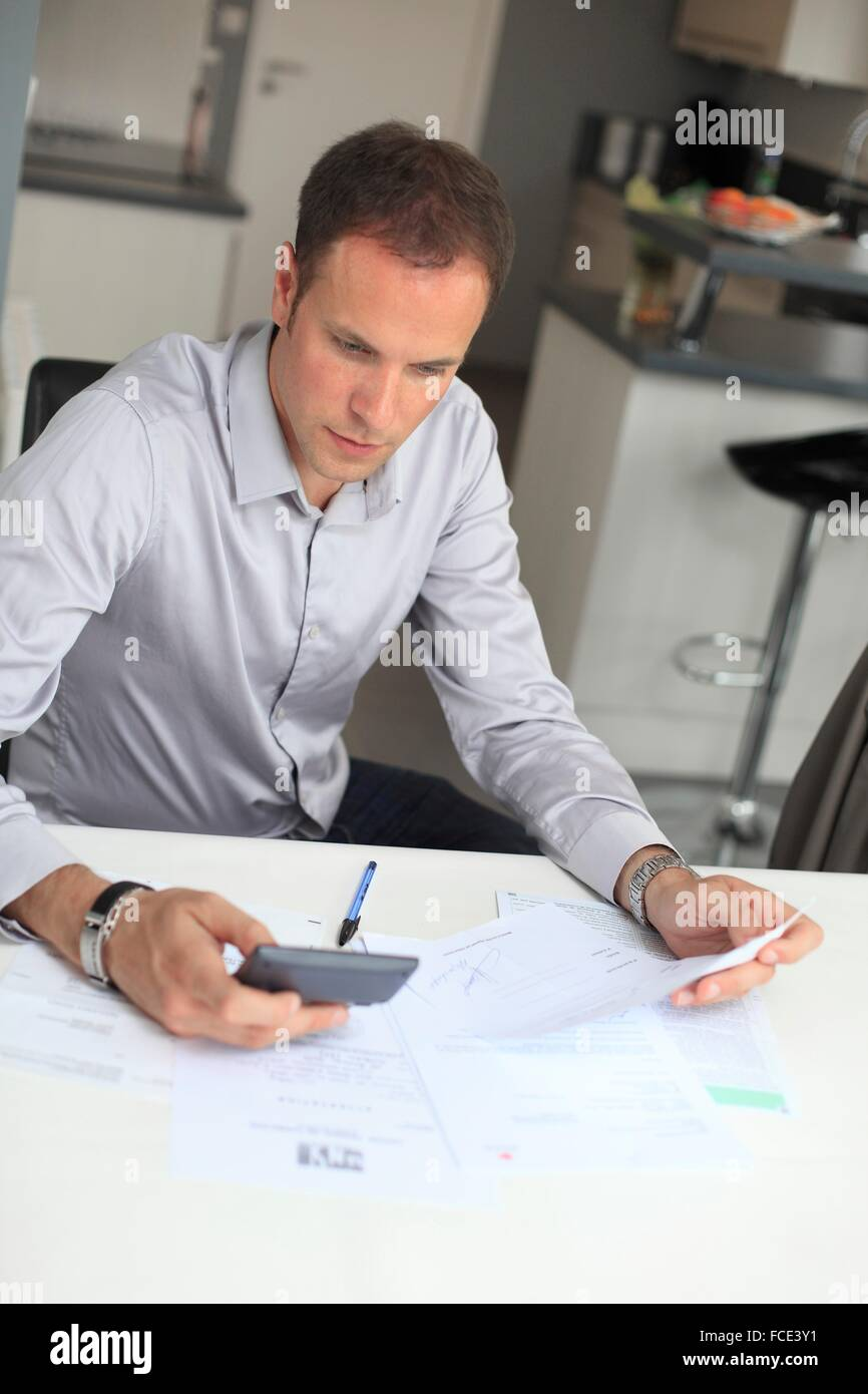 France, young man studying his invoices - Stock Image