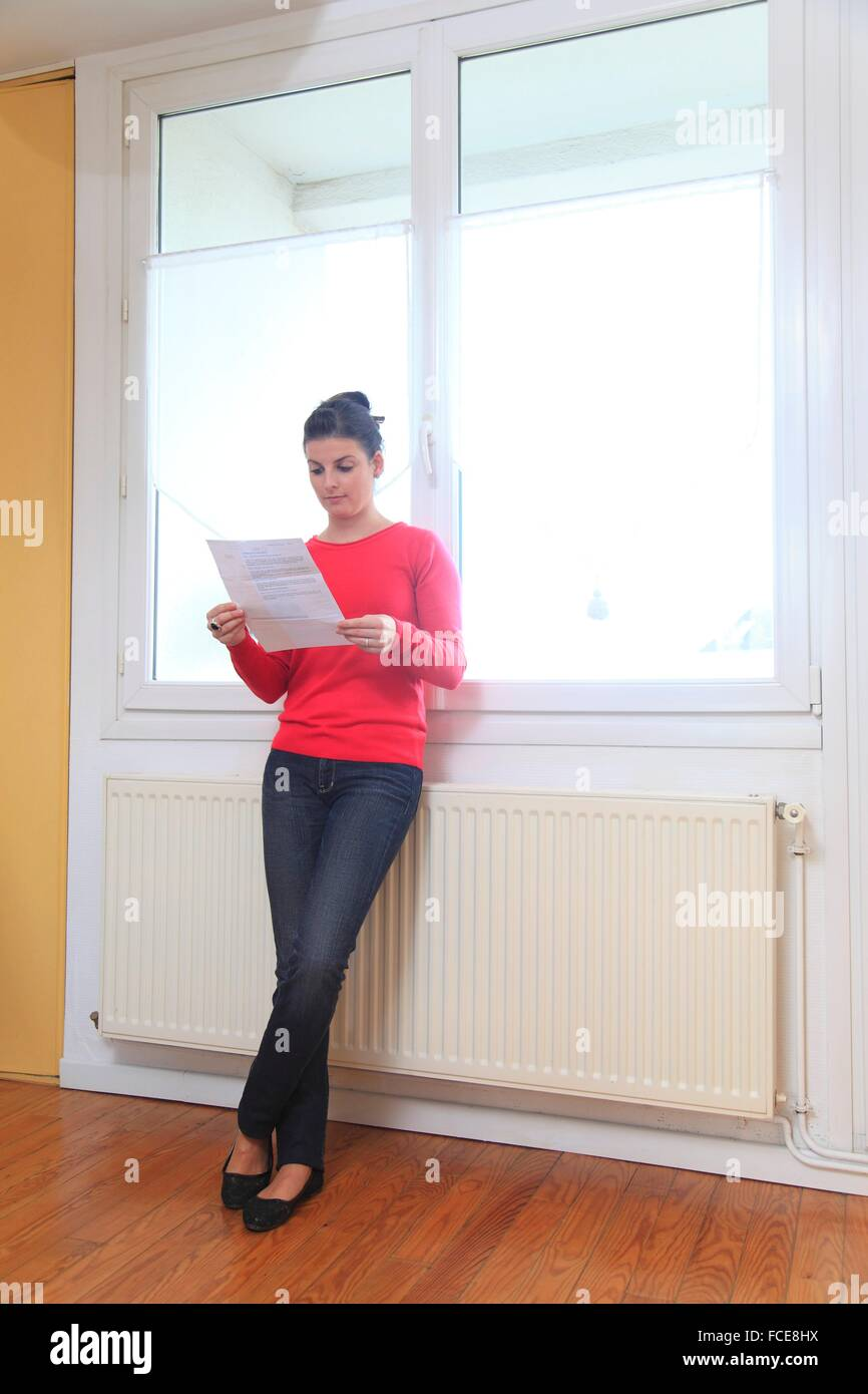 France, young woman and heating - Stock Image