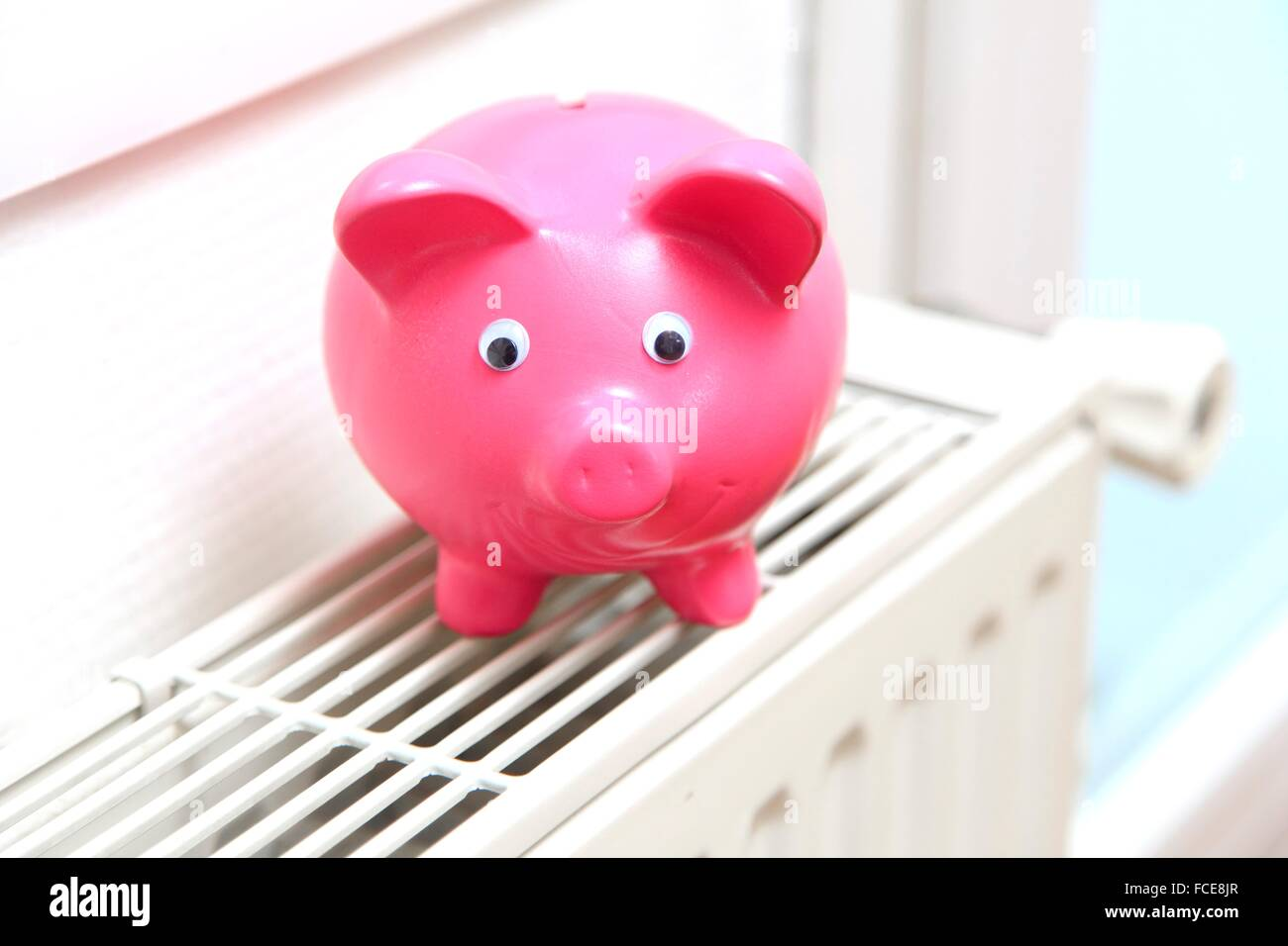 Piggybank on a radiator - Stock Image