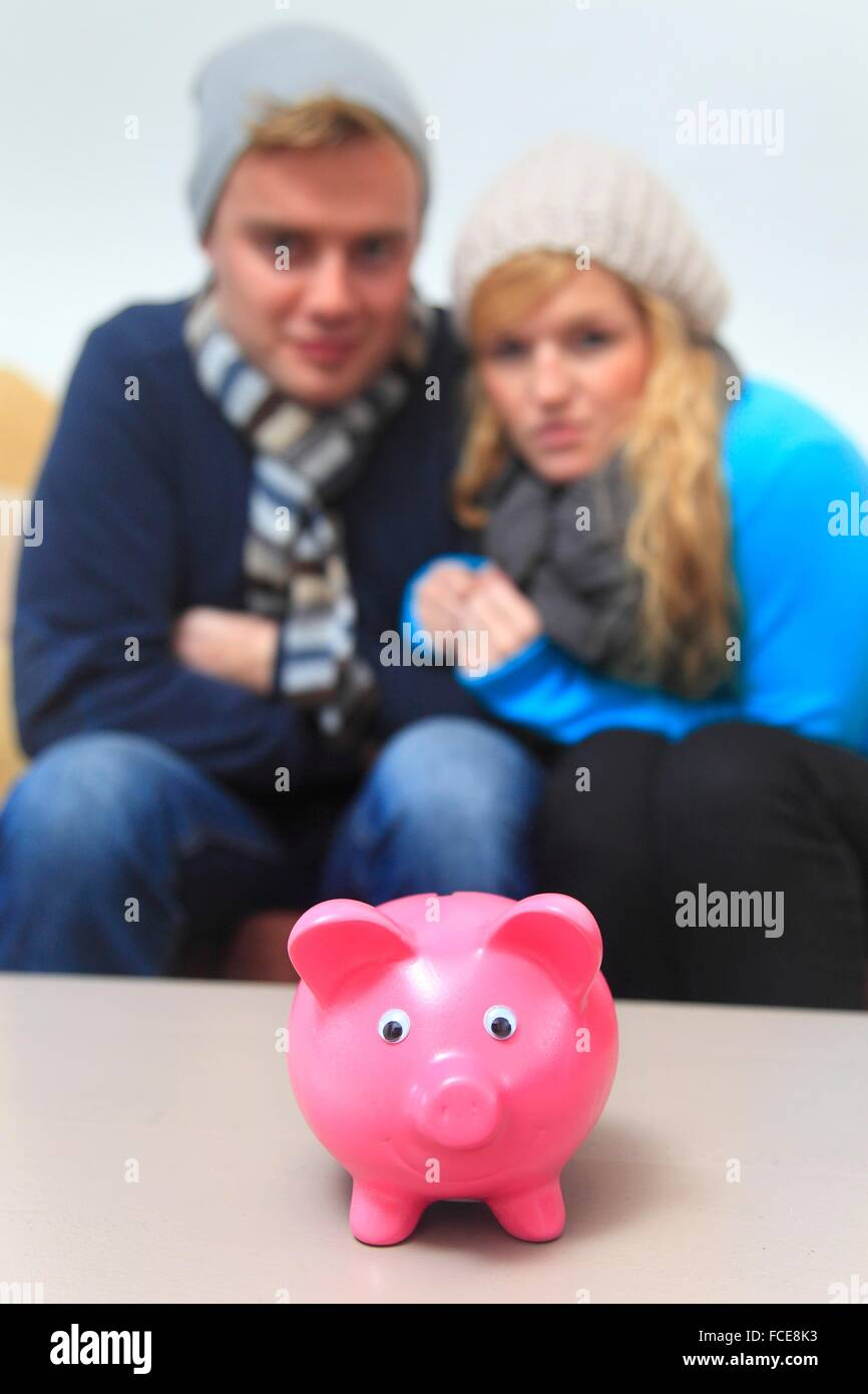 France, young couple dressed warmly, piggybank - Stock Image