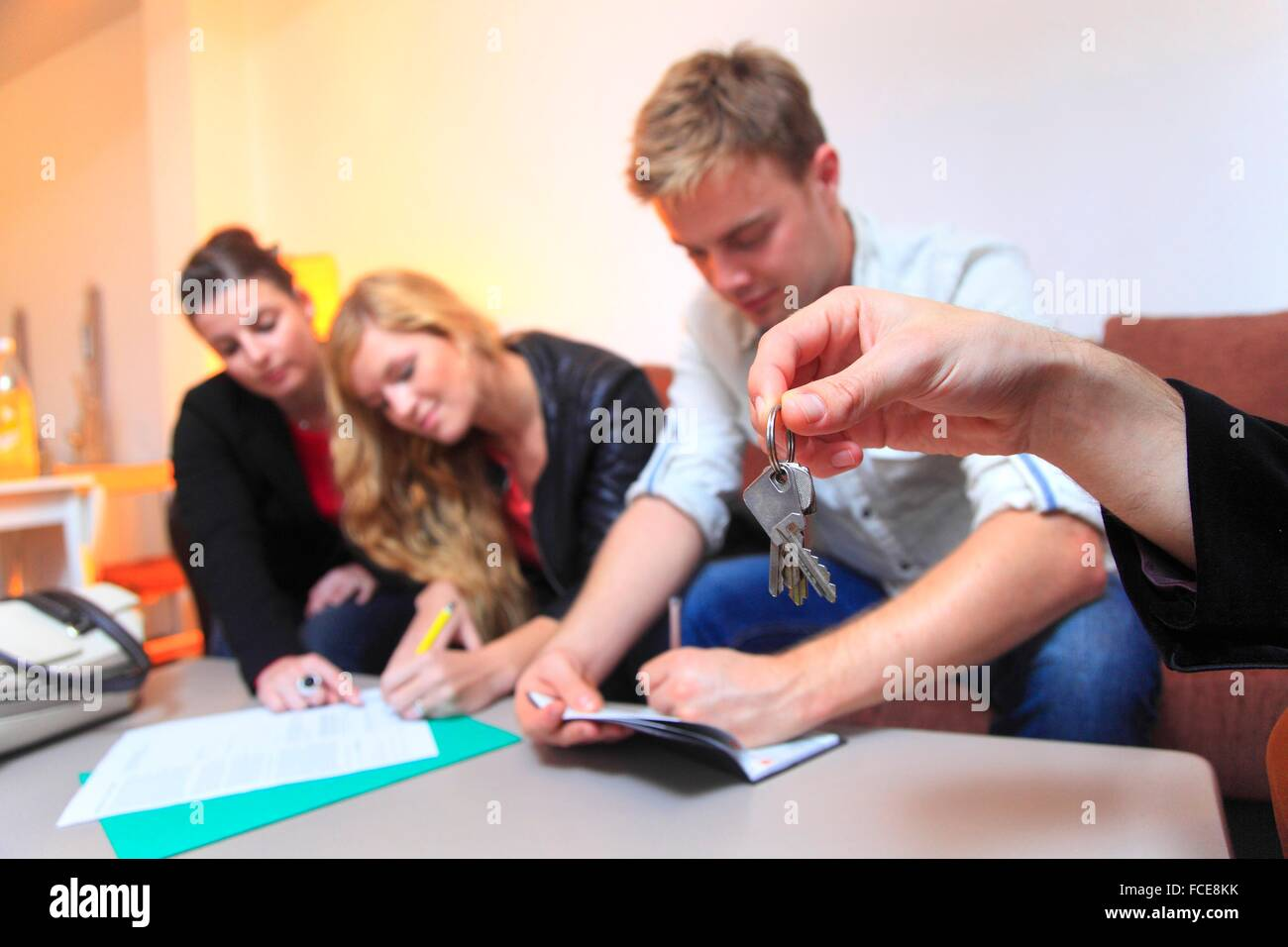 France, couple signing leasing agreement of apartment - Stock Image