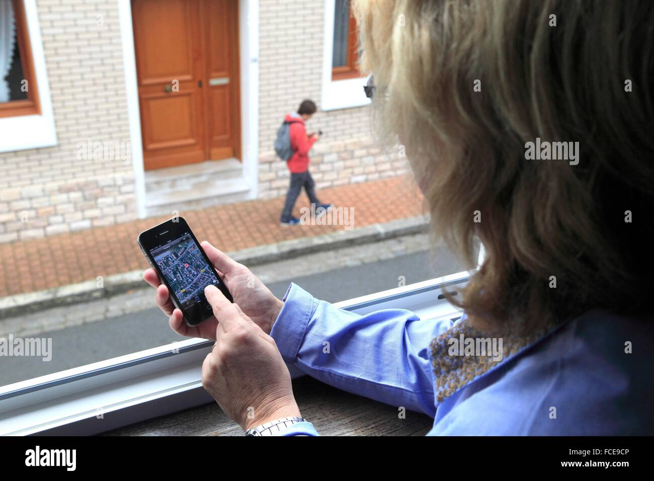 France, mother supervising her son thanks to an application of cellphone localization - Stock Image