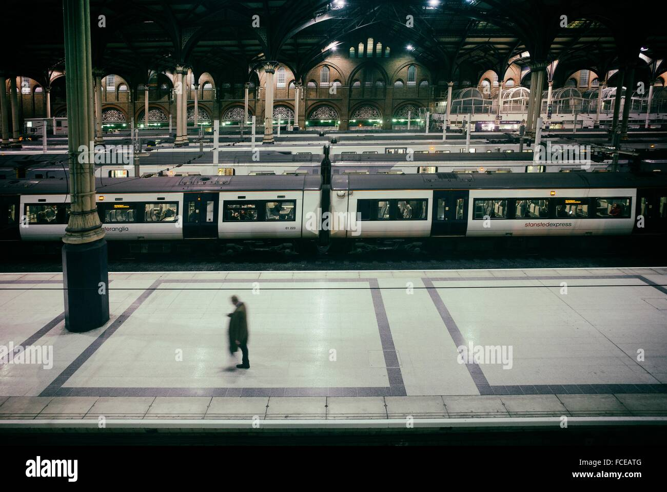 An unrecognizable man, walking down one platform in Liverpool Street train station, with several trains at the background. - Stock Image