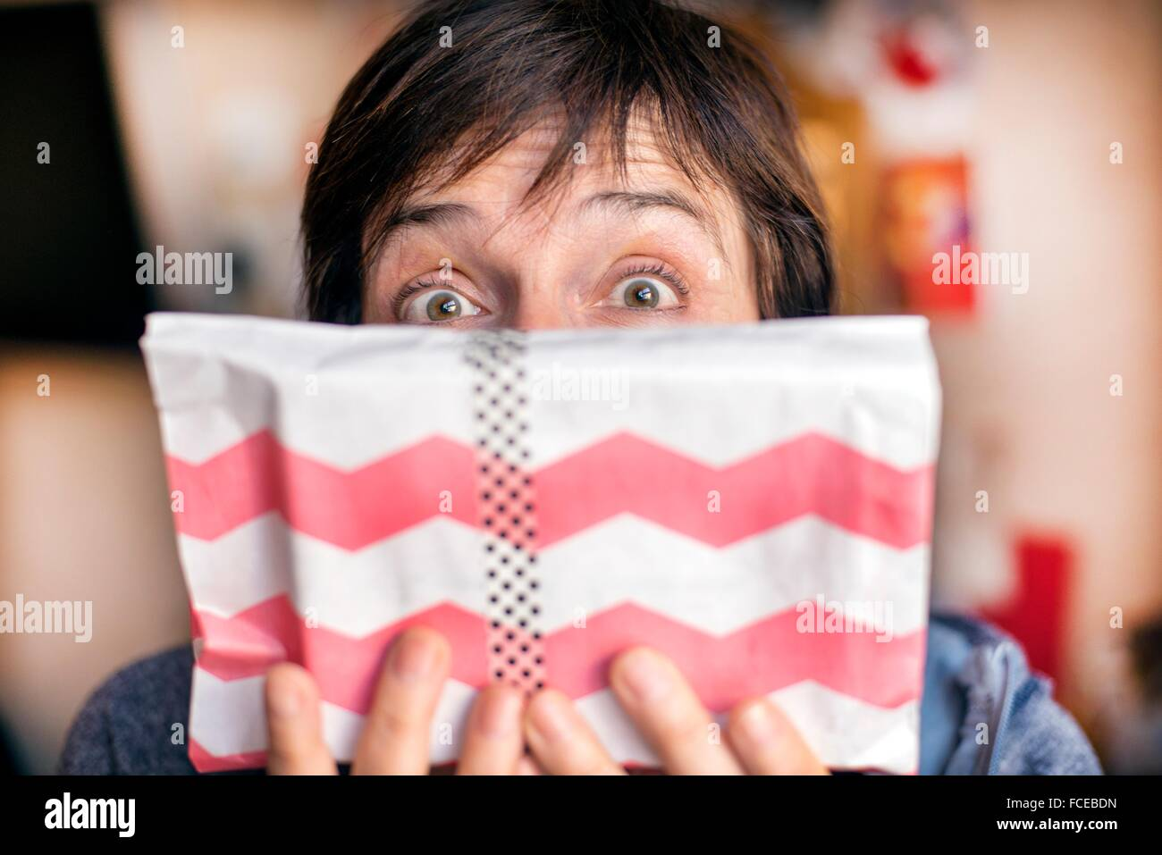 young woman with brown hair and green eyes half face covering himself with a gift with eyes wide open with a surprise - Stock Image
