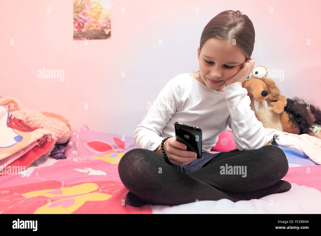 France, little girl and smartphone in her bedroom - Stock Image