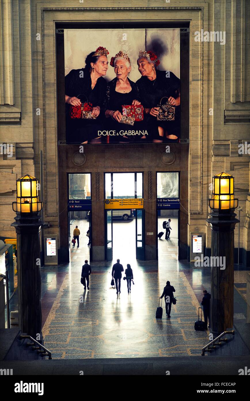 Gate of the Milan train station with people walking and an advert on the wall of Dolce & Gabbana. Milan, Italy, - Stock Image
