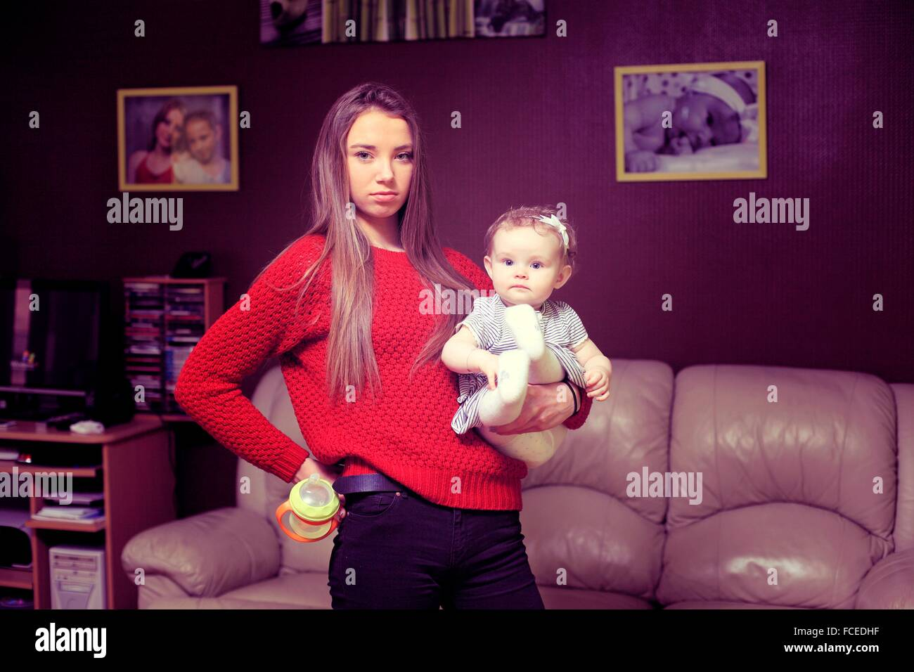France, nanny or very new mother in the living room - Stock Image