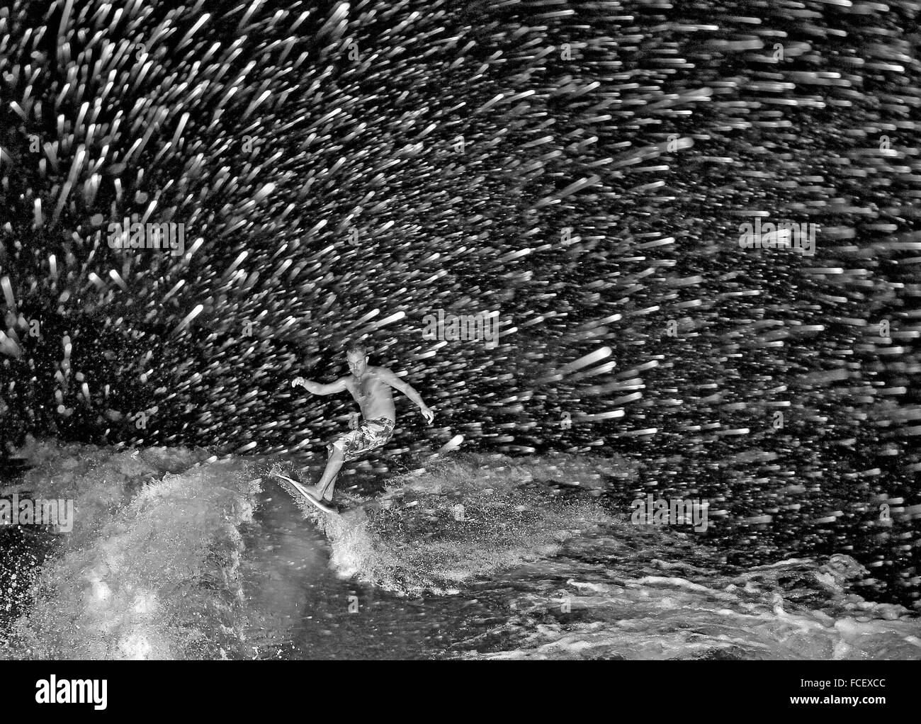 Man Surfing In Sea At Night - Stock Image