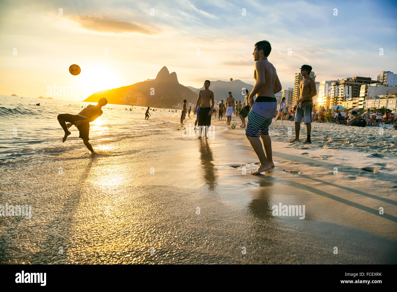 RIO DE JANEIRO - JANUARY 18, 2014: Groups of young Brazilians play keepy uppy beach football, or altinho, at sunset - Stock Image