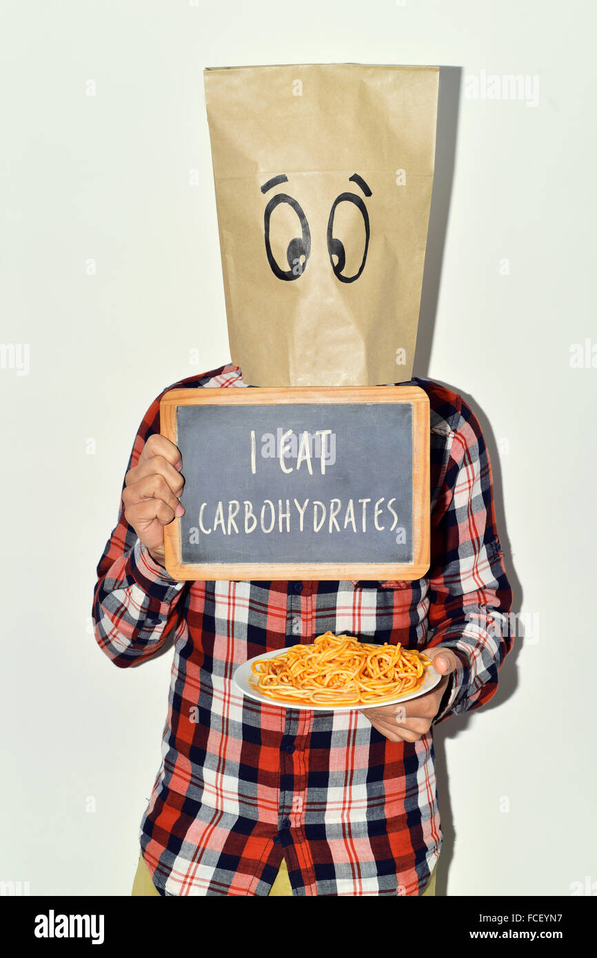 a young caucasian man with a paper bag in his head with a funny face shows a chalkboard with the text I eat carbohydrates - Stock Image